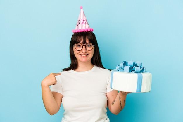 誇りと自信を持って、シャツのコピースペースを手で指している青い背景の人に分離された彼女の誕生日を祝う若い曲線美の女性