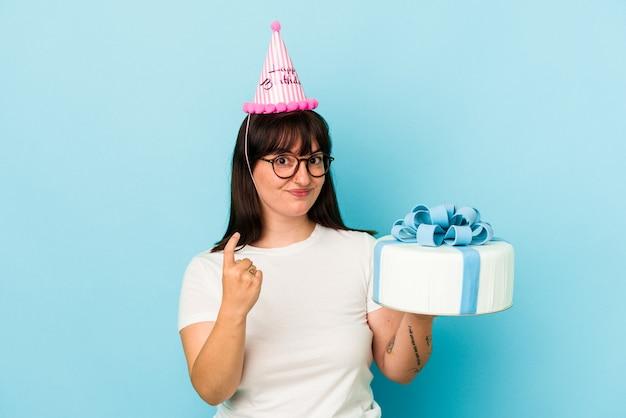 招待状が近づくようにあなたに指を指している青い背景に分離された彼女の誕生日を祝う若い曲線美の女性。