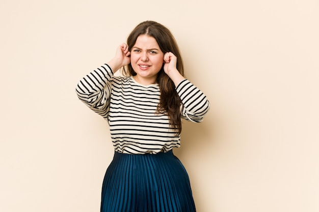 Young curvy woman covering ears with hands.