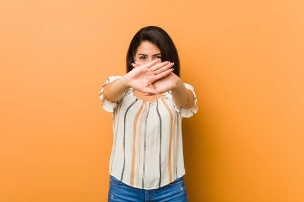 Young curvy woman doing a denial gesture