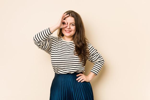 若い曲線の女性は目にokのしぐさを維持することに興奮しています。