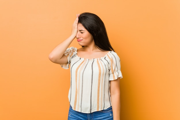 Young curvy woman forgetting something, slapping forehead with palm and closing eyes.
