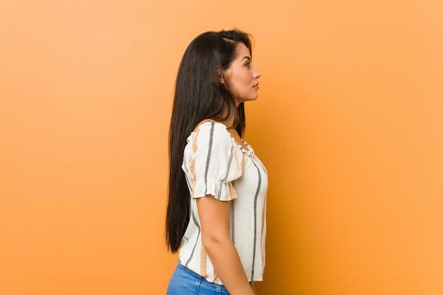 左を見つめる若い曲線の女性、横向きのポーズ。