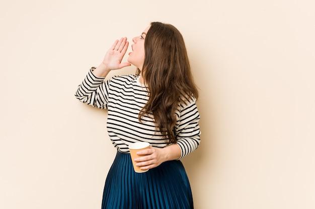 コーヒーを叫び、開いた口の近くで手のひらを保持している若い曲線美の女性。