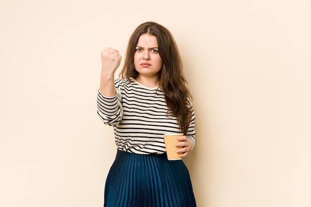 カメラ、積極的な表情にコーヒーを示す拳を保持している曲線の若い女性。