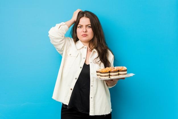 カップケーキを持った若い曲線美の女性はショックを受け、重要な出会いを思い出しました。