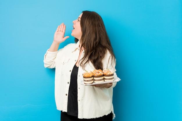 開いた口の近くで叫び、手のひらを保持しているカップケーキを保持している若い曲線美の女性。
