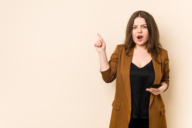 Молодая фигуристая женщина держит телефон, указывая в сторону