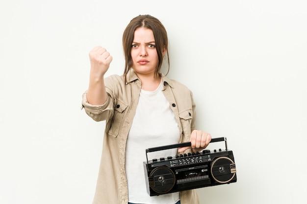 Молодая фигуристая женщина, держащая ретро-радио, показывает кулак на камеру, агрессивное выражение лица.