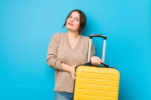目標と目的を達成することを夢見てスーツケースを保持している曲線の若い女性
