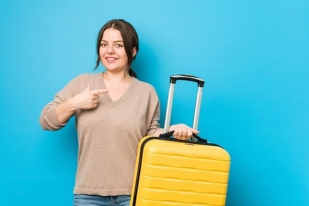 スーツケースを持って笑顔で脇を向いて、空白のスペースで何かを見せている若い曲線美の女性。