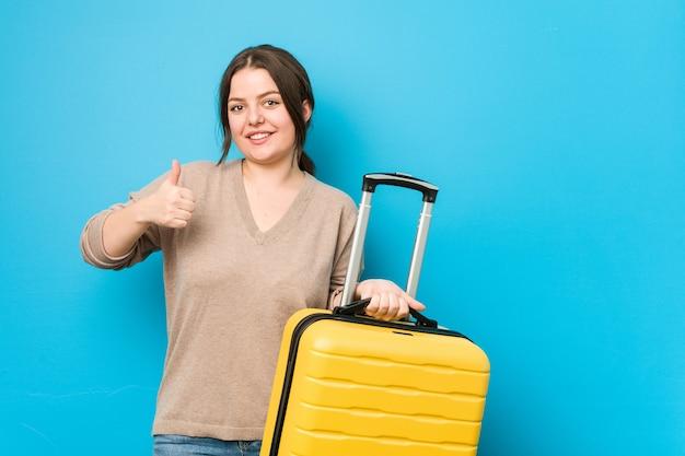 Молодая фигуристая женщина, держащая чемодан, улыбается и поднимает палец вверх