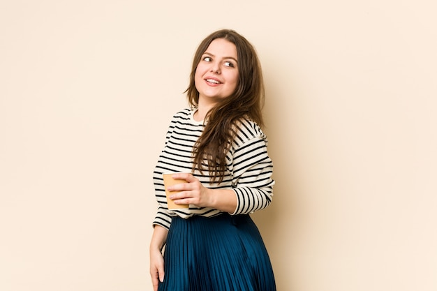 Young curvy woman holding a coffee looks aside smiling, cheerful and pleasant.