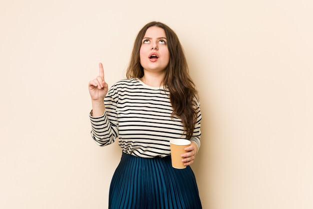 Young curvy woman holding a coffee pointing upside with opened mouth.