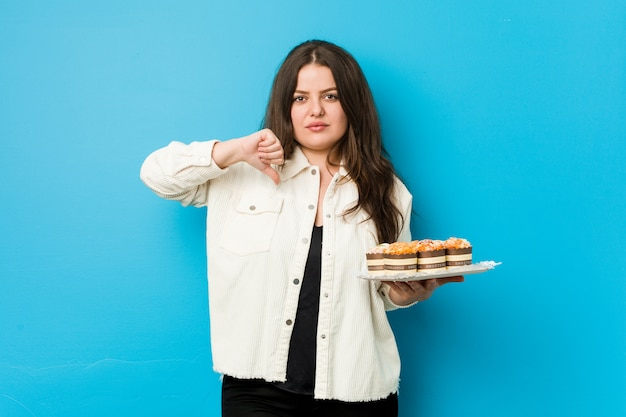 Young curvy woman holding a cupcakes showing a dislike gesture, thumbs down. disagreement concept.