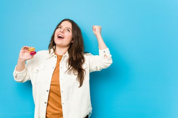Молодая соблазнительная женщина, держащая миндальное печенье, поднимая кулак после победы, концепции победителя.