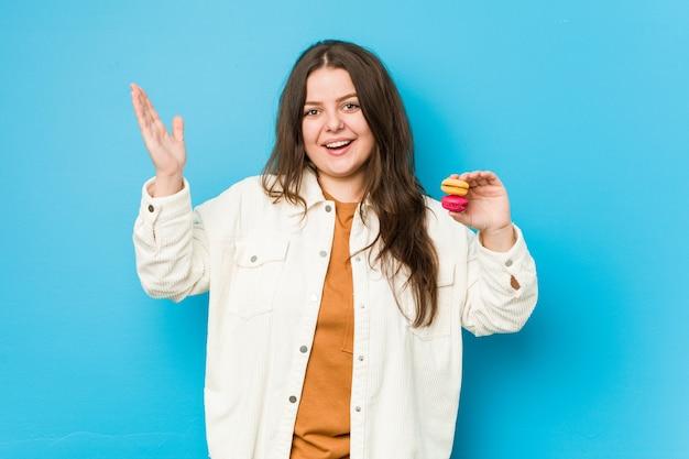 Молодая соблазнительная женщина, держащая миндальное печенье, получает приятный сюрприз, возбужденная и поднимающая руки.