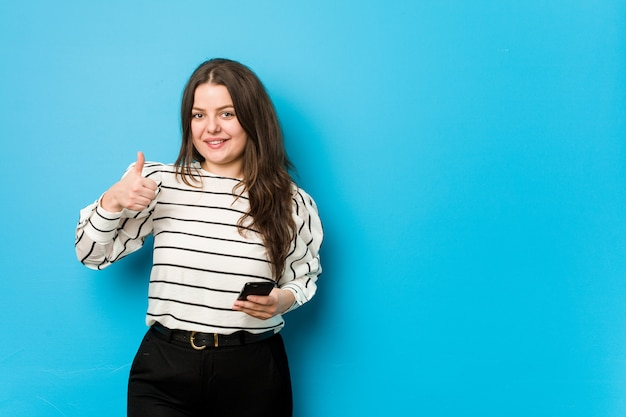 Young curvy woman holding a phone smiling and raising thumb up