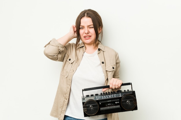 Young curvy woman holding a retro radio covering ears with hands.