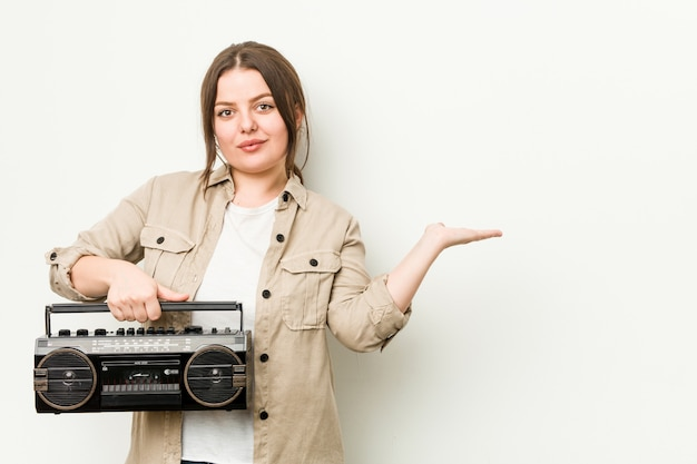 Young curvy woman holding a retro radio showing a copy space on a palm and holding another hand on waist