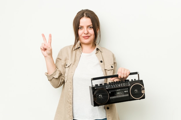Young curvy woman holding a retro radio showing number two with fingers.