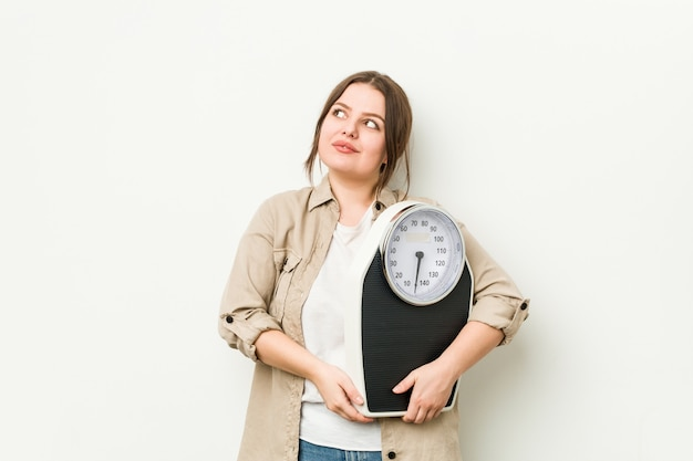 Young curvy woman holding a scale dreaming of achieving goals and purposes
