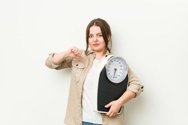 Young curvy woman holding a scale feels proud and self confident, example to follow.