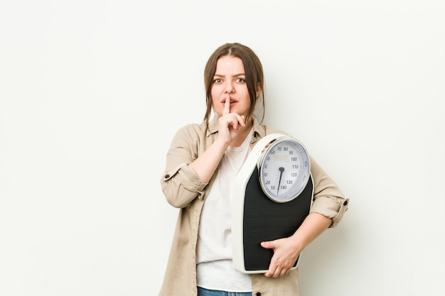 Young curvy woman holding a scale keeping a secret or asking for silence.
