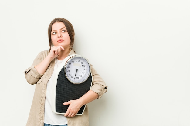 Young curvy woman holding a scale looking sideways with doubtful and skeptical expression.