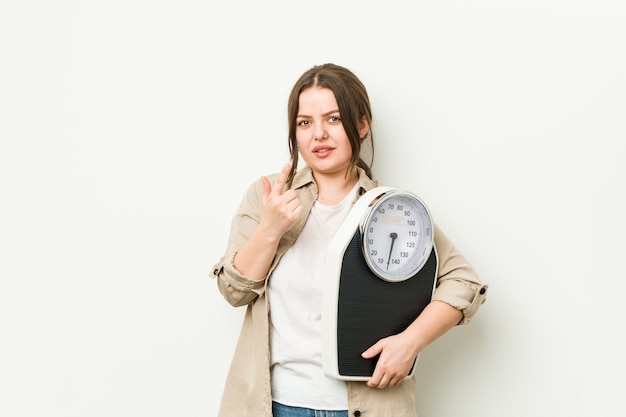 Young curvy woman holding a scale pointing with finger at you as if inviting come closer.