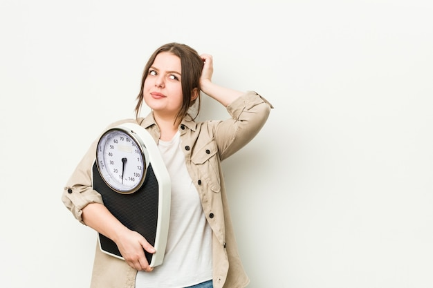 Young curvy woman holding a scale touching back of head, thinking and making a choice.