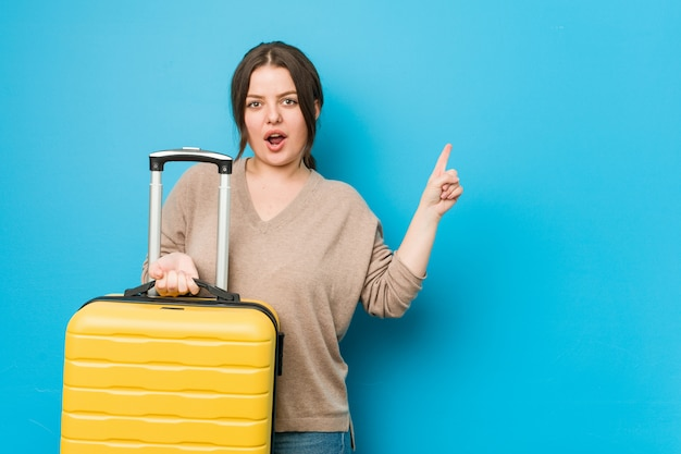 Young curvy woman holding a suitcase pointing to the side