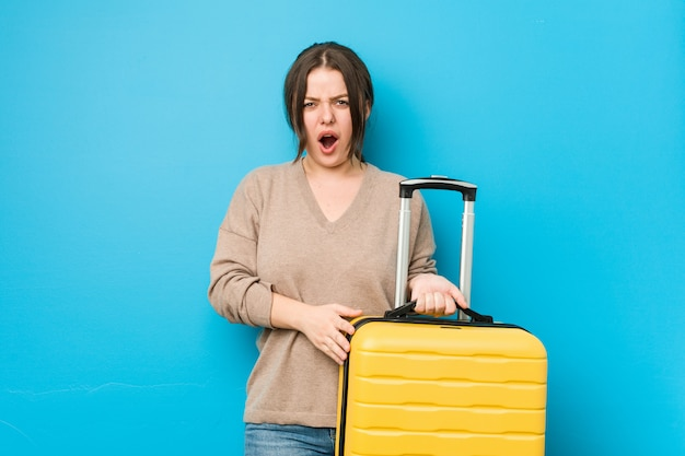 Young curvy woman holding a suitcase screaming very angry and aggressive.