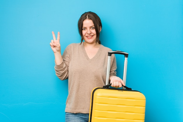 Young curvy woman holding a suitcase showing number two with fingers.