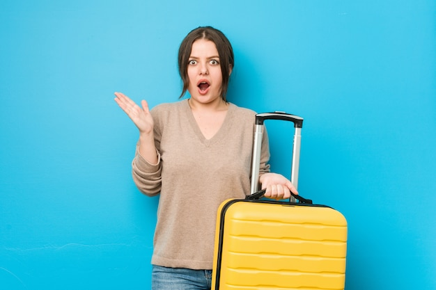 Young curvy woman holding a suitcase surprised and shocked