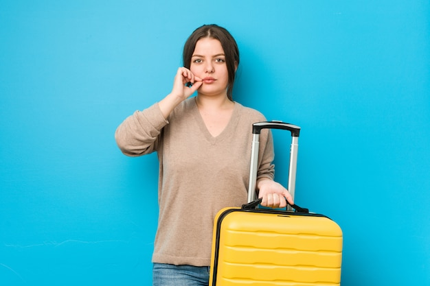 Young curvy woman holding a suitcase with fingers on lips keeping a secret.