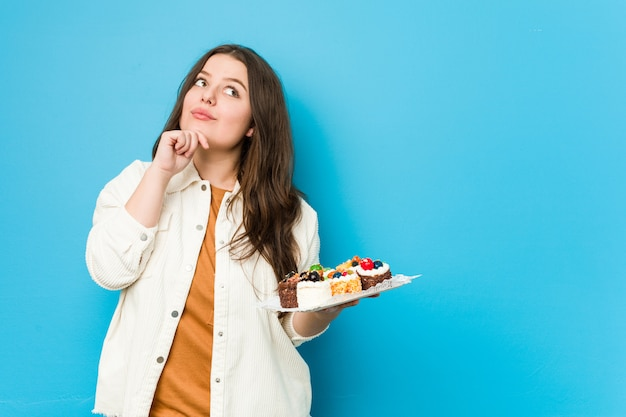 Young curvy woman holding a sweet cakes looking sideways with doubtful and skeptical expression.