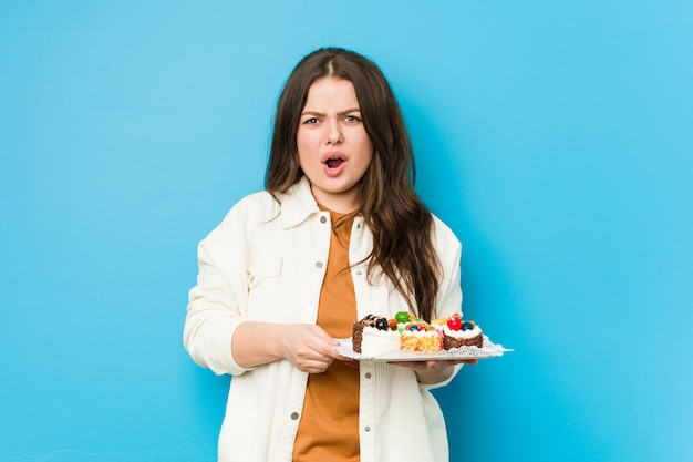 Young curvy woman holding a sweet cakes screaming very angry and aggressive.