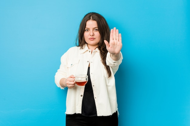 Young curvy woman holding a tea cup standing with outstretched hand showing stop sign, preventing you.