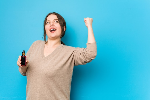 Young curvy woman holding a vaporizer raising fist after a victory
