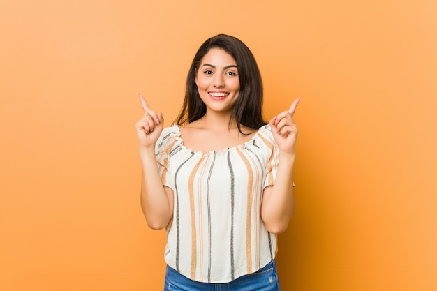 Young curvy woman indicates with both fore fingers up showing a blank space.