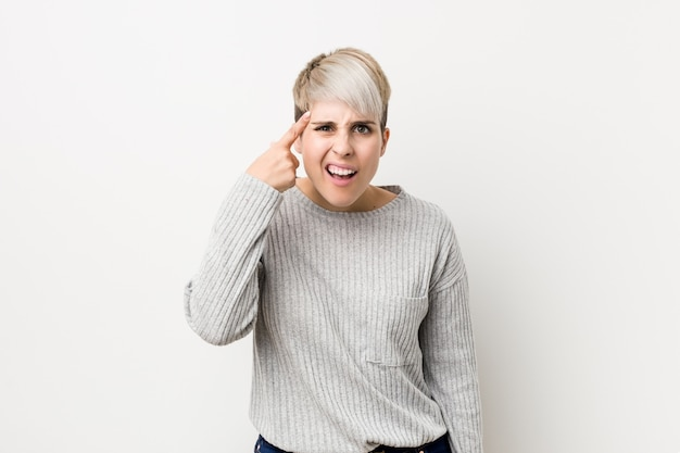 Young curvy woman isolated on white background showing a disappointment gesture with forefinger.