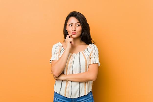 疑わしいと懐疑的な表情で横に探している若い曲線の女性。
