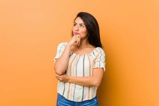 疑いと懐疑的な表情で横に探している若い曲線の女性。