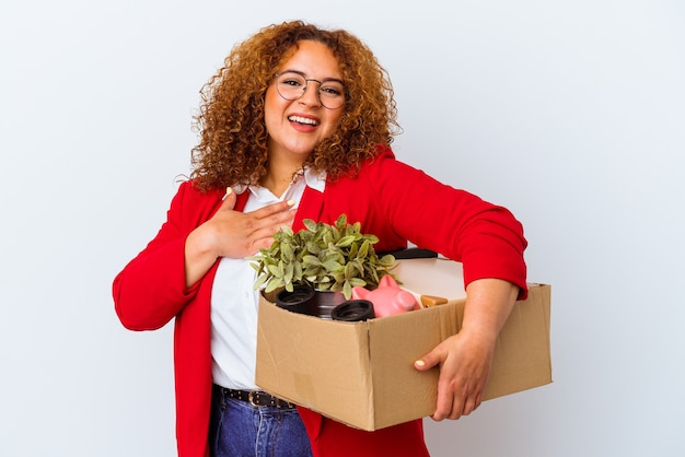 Young curvy woman moving to a new home isolated on white background laughs out loudly keeping hand on chest.