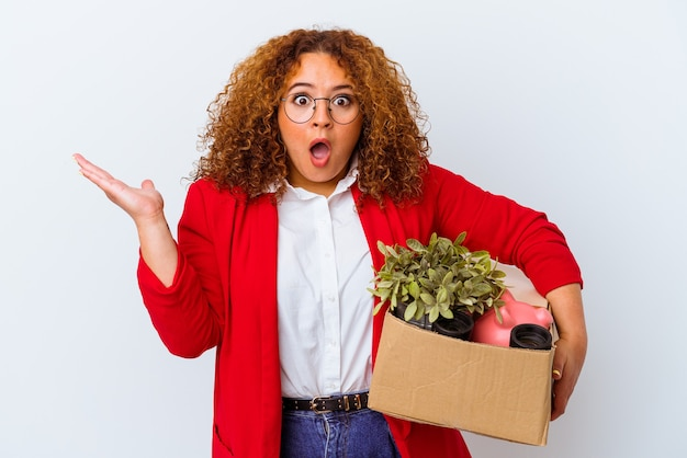 Young curvy woman moving to a new home isolated on white background surprised and shocked.