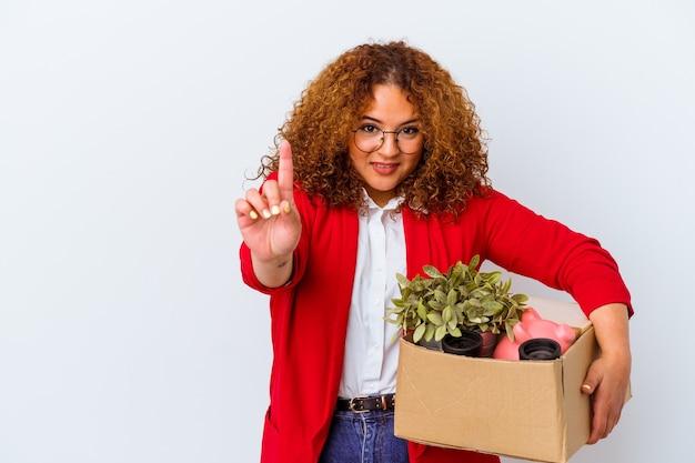 Молодая фигуристая женщина переезжает в новый дом на белом фоне, показывая номер один пальцем.