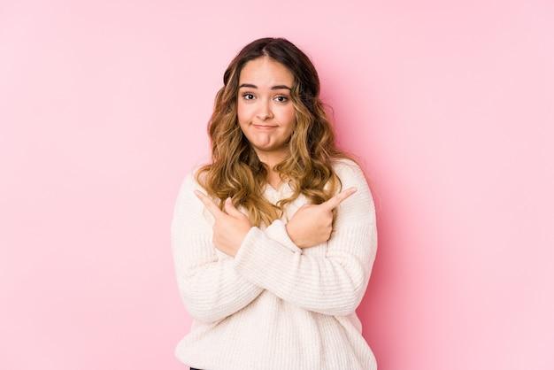 ピンクの壁でポーズをとって若い曲線の女性が横に分離されたポイントは、2つのオプションから選択しようとしています。