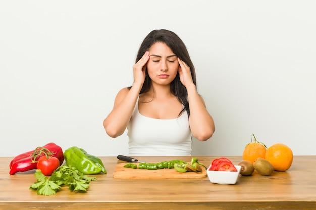 Молодая соблазнительная женщина готовит здоровую еду, касаясь висков и имея головную боль.
