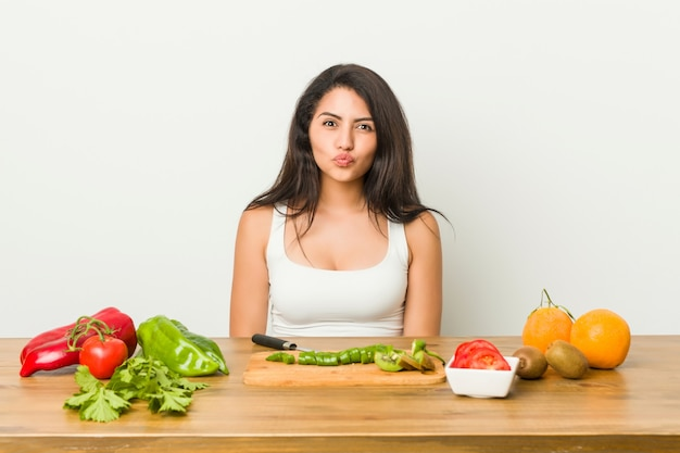Young curvy woman preparing a healthy meal blows cheeks, has tired expression. facial expression concept.